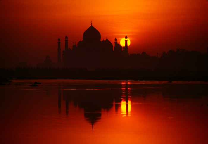 Taj Mahal at sunrise Agra, India Cat: #94-38-25 One of the most photographed buildings in the world, the Taj Mahal live up to it's reputation as one of the world's most beautiful buildings. I have never seen the building photographed from this angle on the banks of the Yamuna River (a branch of the acred Ganges) with the rising sun directly behind.